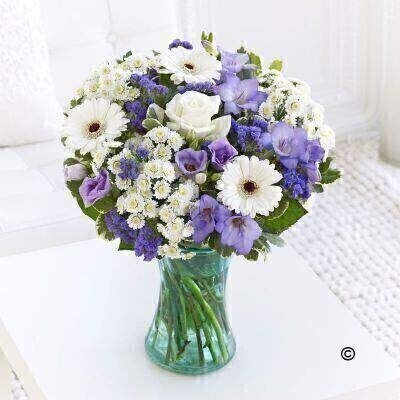 A new little boy has arrived and itandrsquo;s time to celebrate! Weandrsquo;ve chosen a beautiful selection of fresh blooms in cool lilac and blue shades partnered with crisp white to create a stunning vase of flowers that they are sure to love. Featuring white spray chrysanthemums - purple statice - white germini - lilac lisianthus - white large headed rose - and purple freesia with salal and pittosporum - arranged in a blue swirl Nigella vase and trimmed with a blue button heart tag.
