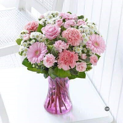 Beautiful baby girls and the softest pink are a partnership made in heaven. Thatandrsquo;s why weandrsquo;ve chosen an array of fresh blooms in light pink shades to create this stunning vase arrangement. The cute gingham heart is a charming finishing touch that is sure to prompt a smile. Featuring pink carnations - pink germini - pink large headed rose - white spray chrysanthemums and light pink spray carnation with salal and pittosporum - arranged in a pink swirl glass vase and trimmed with a pink button heart tag.