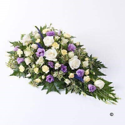 This beautiful floral spray features shades of blue - lilac - cream and white. Large-headed roses - lisianthus - spray carnations - spray roses and Veronica are carefully arranged with leather leaf and pittosporum.