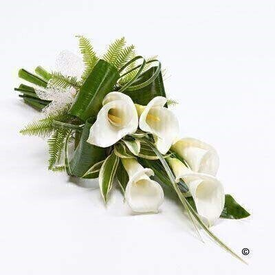 Classic white calla Lily tied with a natural ribbon are complemented by folded aspidistra leaves and dracaena to create this contemporary sheaf.