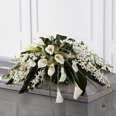 White Dendrobium orchids - white calla Lily - green hydrangea and a variety of lush green leaves are expertly arranged to create a very graceful casket spray.