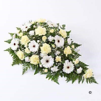 This classic large teardrop spray features soft lemon carnations and snow white germini. Tiny white gypsophila flowers and intricate leather leaf foliage give this arrangement extra detail.