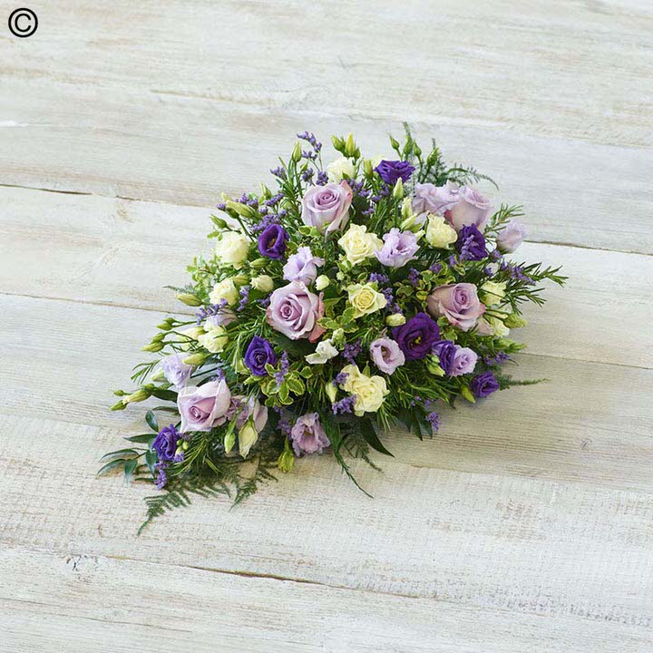 This delicate casket spray arrangement includes pure white calla Lily and large-headed roses contrasted with sweetly fragrant lilac freesia - September flowers and purple lisianthus. The display is trimmed with China grass - ruscus - asparagus fern and ivy trails.