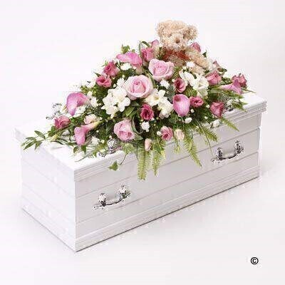 Bramble Bear sits amongst a sea of pink and white flowers - creating a fitting tribute for a little girl. Roses and calla Lily in soft pink shades are arranged with white freesia - September flowers and deep pink lisianthus and finished with China grass - ruscus - ferns and ivy trails.