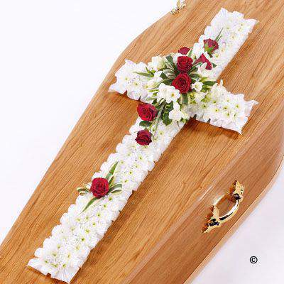 This classic cross is covered with a mass of white Spray Chrysanthemums. A spray of red roses, white freesias and dracaena leaves completes this traditional design.