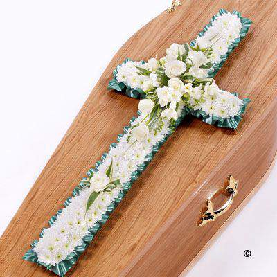 This classic cross is covered with a mass of white Spray Chrysanthemums. A spray of white roses - white freesias and dracaena leaves completes this traditional design.