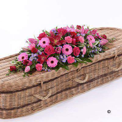 This bright casket spray feautring a classic selection of flowers in pink - red and lilac includes large-headed Rose - carnations - Gerbera and Oriental Lily complemented by luxurious foliages.
