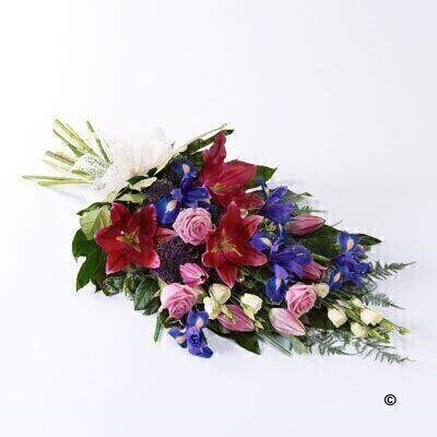 The soft blue shades of iris are complemented by pink Oriental liles - pink large-headed roses and cream lisianthus in this classic sheaf - which is tied together with a cream ribbon.