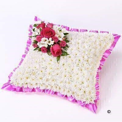 A classic cushion-shaped design created using a mass of white double spray chrysanthemums and finished with a spray of cerise roses and white freesias and a pink ribbon trim.