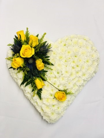 A classic heart-shaped design covered with a mass of white double spray chysanthemums and finished with a spray of yellow large-headed roses - eryngium and ruscus.