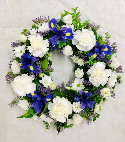 A classic selection of flowers including irises - carnations and spray chrysanthemums in blues and whites are nestled into this traditional circular wreath.