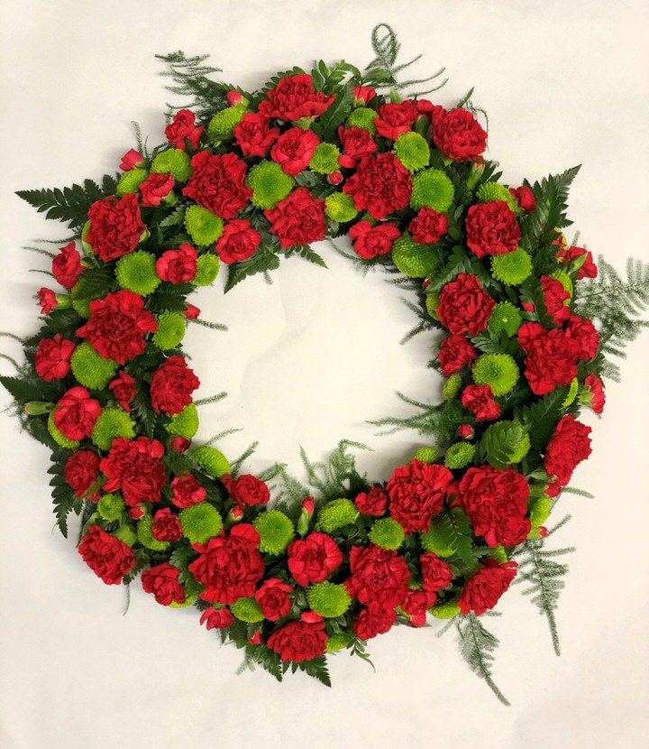 A classic selection of flowers including carnations and spray chrysanthemums in reds and greens are nestled into this traditional circular wreath.