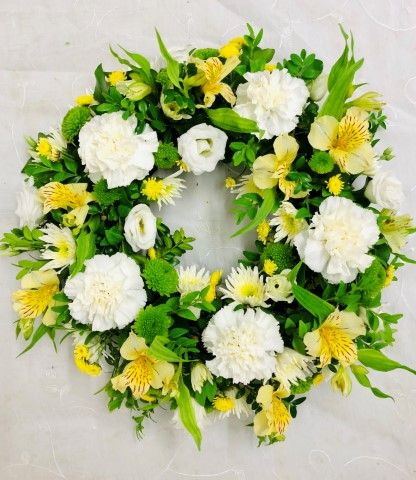 A classic selection of flowers including irises - carnations and spray chrysanthemums in yellows and creams are nestled into this traditional circular wreath.