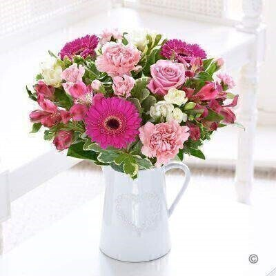 We've chosen a charming mix of the prettiest flowers in an array of pink tones to create this gorgeous arrangement. With cheery germini elegant alstroemeria and wonderfully fresh scented freesia this is a gift they'll love. The jug makes a delightful keepsake too.<br><br>Featuring 2 cerise alstroemeria 2 pink carnations 3 white freesia 3 cerise germini a pink large headed rose and 2 pink spray carnations with salal and pittosporum presented in a white ceramic jug with embossed heart design.<br><br>This product contains 13 stems.<br><br>Approximate Product Dimensions: Height: 35cm Width: 25cm