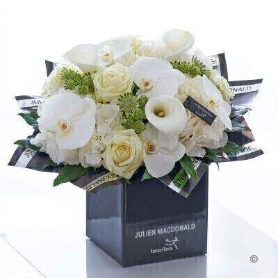 This heavenly bouquet is a pristine presentation of elegant simplicity. The very finest quality fresh flowers in cream white and ivory are expertly hand-tied to stunning effect. Sleek calla lilies and orchids contrast with intricate rose and hydrangea petals resulting in an elegant indulgent and infinitely beautiful gift.<br><br>Featuring 3 white glittered hydrangea 5 white large headed roses 3 white calla lilies 5 white phalanopsis orchids and 3 white astrantia with aralia and salal presented in Julien Macdonald foil wrap and a dual-branded gift box with designer gift tag and ribbon. This hand-tied is tightly constructed to create a neat compact posy of flowers. <br><br>This product contains 16 stems. <br><br>Featuring 3 white glittered hydrangea 5 white large headed roses 3 white calla lilies 5 white phalanopsis orchids and 3 white astrantia with aralia and salal presented in Julien Macdonald foil wrap and a dual-branded gift box with designer gift tag and ribbon. This hand-tied is tightly constructed to create a neat compact posy of flowers. <br><br>This product contains 16 stems. <br><br>Approximate Product Dimensions: Height: 45cm Width: 44cm