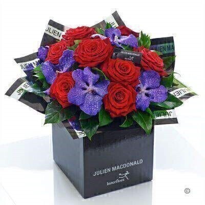Two of the most enchanting flower varieties feature in this sumptuous bouquet. A striking partnership of the finest quality exotic purple orchids partnered with magnificent velvety roses in classic red — this is a magical gift that is both naturally stylish and wonderfully luxurious.<br><br>Featuring 5 purple Vanda orchids and 8 red large headed roses with aralia salal and ruscus presented in Julien Macdonald foil wrap and a dual-branded gift box with designer gift tag and ribbon. This hand-tied is tightly constructed to create a neat compact posy of flowers.<br><br>This product contains 13 stems. <br><br>Approximate Product Dimensions: Height: 38cm Width: 34cm