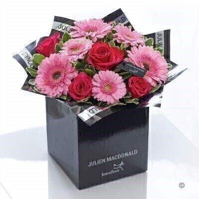 Wonderfully feminine with a dash of glamour this designer floral gift is just perfect for a special occasion. These gorgeous gerbera and fresh germini in exquisite pink tones look simply sensational with richly coloured cerise roses. A sprinkling of glitter gives extra sparkle.<br><br>Featuring 3 glittered pink gerbera 3 glittered pink germini and 4 cerise large headed roses with pittosporum and salal presented in Julien Macdonald foil wrap and a dual-branded gift box with designer gift tag and ribbon. This hand-tied is tightly constructed to create a neat compact posy of flowers.<br><br>This product contains 10 stems. <br><br>Approximate Product Dimensions: Height: 38cm Width: 36cm