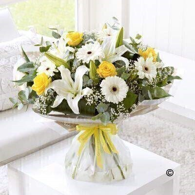 Large version of the Congratulations Hand-Tied. andnbsp;Send your congratulations in style with this bright and sunny bouquet. Weandrsquo;ve carefully hand-tied a selection of white lilies and germini and added radiant yellow roses for a perfect contrast. Tiny white gypsophila flowers give this gift an extra touch of magic. Featuring white germini - yellow large-headed roses - white Oriental lilies and white gypsophila - hand-tied with folded aspidistra leaves - eucalyptus and salal - wrapped and trimmed with yellow andlsquo;Congratulationsandrsquo; ribbon.