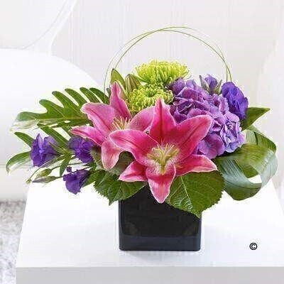 Here is a beautiful gift of flowers that encapsulates elegance and creativity at its very best. The rich velvety pink Oriental lilies are paired with lavish purple and lime green shades to create a vibrant yet ultimately sophisticated look. Featuring 2 green bloom chrysanthemums - 2 purple lisianthus - a purple hydrangea - dark pink Oriental lilies and 2 philodendron xanadu - with aspidistra leaves and steel grass - presented in a black cube vase.