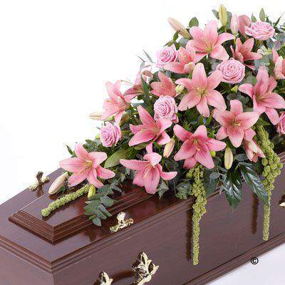 Beautiful Asiatic Lily and large-headed Rose in pretty pink are used to create this elegant casket spray. The fresh flowers are enhanced with trails of green amaranthus as well as ruscus - aralia leaves and eucalyptus.