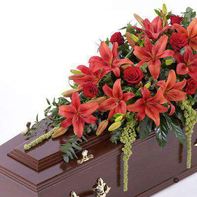 This striking casket display features a selection of fresh Asiatic Lily and large-headed Rose in shades of rich red. The flowers are carefully arranged with amaranthus - ruscus - eucalyptus and aralia leaves.