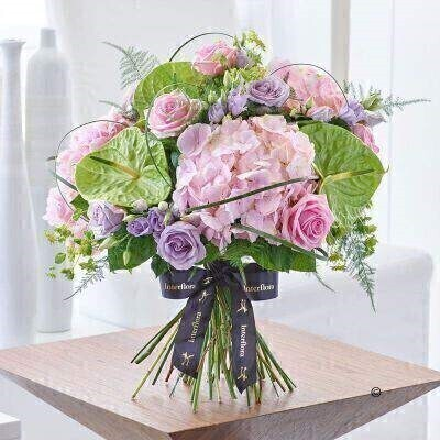 THIS PRODUCT COMES HAND ARRANGED AND GIFT WRAPPED IN A WATER BUBBLE PRESENTED IN A BOX.<br><br>This beautiful design takes classic uninhibited styling and soft feminine colours to create a romantic gift with timeless appeal. From palest pink to dreamy lilac this selection of perfect roses and hydrangea makes a sensational focal point that draws the eye to its delicate beauty.<br><br>Featuring pale pink Verena hydrangea green Midori anthurium lilac Rosita Lavender double lisianthus large headed pink Heaven roses and lilac Ocean Song large headed roses with bupleurum asparagus fern steel grass and salal expertly hand-tied and presented in luxurious packaging for maximum impact when your gift is delivered.<br><br>This product contains 20 stems.<br><br>Approximate Product Dimensions:<br><br>Height: 48cm Width: 49cm