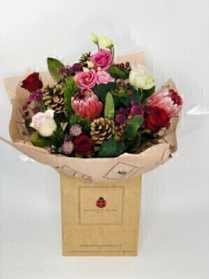 Modern Festive Bouquet in WaterHand arranged by our florists in a box to form a luxury presentation bouquetTo give you the best occasionally we may make substitutesOur flowers backed by our 7 days freshness guaranteeApproximate dimensions 38x40cmThis product is available for UK delivery 9th - 24th DecemberThis festive luxury bouquet of flowers with a modern twist is a delightful choice for a Christmas gift or December Birthday.Featuring 3 red large-headed roses 2 lilac large-headed roses 3 pink astrantia 2 skimmia 3 purple spray chrysanthemums 2 dark pink proteas 3 pinecones and 2 pink lisianthus hand arranged with mixed foliage and presented in eco-friendly gift wrap and eco-friendly presentation box. Plus all our bouquets and plants have a small wooden ladybird hidden in somewhere so dont forget to spot the ladybird on our social media pages!Liverpool Flower DeliveryWe offer advanced booking flower delivery same day flower delivery 3 hour Flower delivery guaranteed AM PM or Evening Flower Delivery and we are now offering Sunday Flower Delivery.The best florist in LiverpoolCome to Booker Flowers and Gifts Liverpool for your Beautiful Flowers and Plants if you really want to spoil we also have a great range of Local Gin Wines Champagne Balloons Vases and Chocolates that can be delivered with your flowers. To see the full range see our extras section. You can trust Booker Flowers and Gifts can deliver the very best for you.