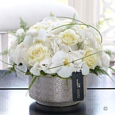 This exquisite arrangement of orchids roses and hydrangea is simply breath-taking. By choosing the finest quality flowers in purest white tones the natural beauty of each one really shines out. This is a truly stunning gift that will look sensational in their home.Featuring white Snowball hydrangea white Cambridge phalaenopsis orchid stems and white Avalanche large headed roses with flexi grass and asparagus fern expertly arranged in a gold ceramic planter and finished with luxury gold and black gift wrapping for maximum impact when your gift is delivered.This product contains 15 stems.Approximate Product Dimensions: Height: 24cm Width: 34cm