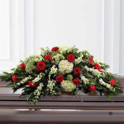 Rich red Rose and carnations are an eye-catching addition to a bed of white hydrangea - larkspur - antirrhinum - Queen Anne's lace and choice foliage to create a beautiful casket spray.