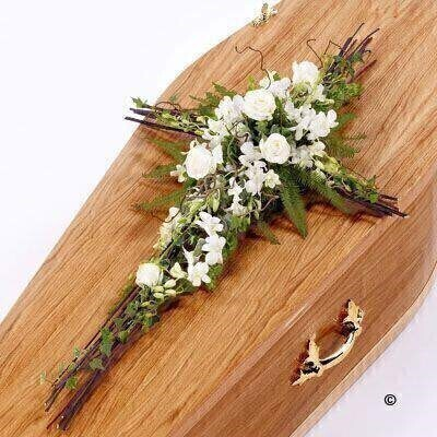 Striking white Dendrobium orchids - white large-headed roses and trailing ivy are entwined around twisted willow - hazel and cornus to create this contemporary cross.