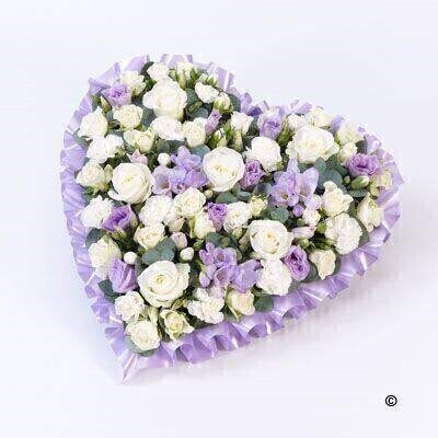 A heart-shaped design in soft pastel lilac and white shades including roses - spray roses - lisianthus - spray carnations and scented freesia.