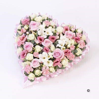 A heart-shaped design in soft pastel pink and white shades including roses - spray roses - lisianthus - spray carnations and scented freesia.