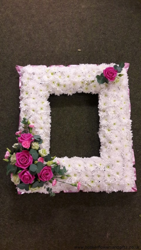 This very personal floral tribute features a space to place your photo of your loved one surrounded by a frame of fresh flowers. An abundance of white double spray chrysanthemums are contrasted with a small spray of roses mixed flowers and foliage (spray can be made in any colour) and trimmed with ribbon.