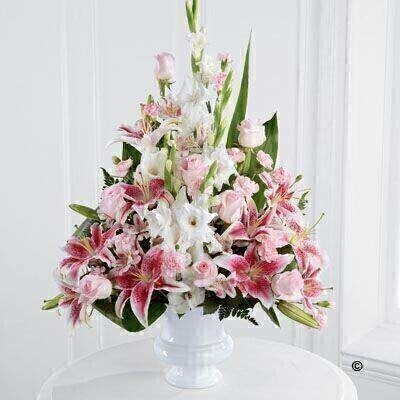 The beautiful arrangement is an exquisite display of serene wishes and grace. Soft pink roses - alstroemeria and carnations are arranged amongst pink Oriental Lily and white gladioli - along with lush greens in a white plastic urn.