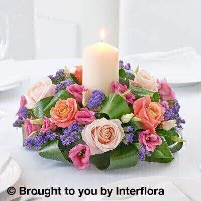 Pink and Purple Flowers  Table Centrepiece <br><br>Liverpool Flower Delivery<br><br>We offer advanced booking flower delivery same day flower delivery 3 hour Flower delivery guaranteed AM PM or Evening Flower Delivery and we are now offering Sunday Flower Delivery. .<br><br><ul><li>Hand arranged by our florists</li><li> To give the best occasionally we may make substitutes</li><li> Our flowers backed by our 7 days freshness guarantee</li><li> Approximate dimensions 30cm diameter 22cm High</li><li> This product is available for delivery throughout the UK</li></ul><br><br>THIS ARRANGMENT IS IN FLORAL FOAM AND COMES PRE ARRANGED IN CONTAINER The complementary and contrasting colours in this enchanting arrangement are a delight. Peach fuchsia pale pink and violet tones co-ordinate beautifully to create a fresh and modern centrepiece.<br><br>Featuring 2 pink lisianthus 3 pale pink large headed roses and 3 peachy pink large headed roses with purple statice and aspidistra leaves and an ivory church candle.<br><br>The best florist in Liverpool<b><b>Come to Booker Flowers and Gifts Liverpool for your Beautiful Flowers and Plants if you really want to spoil we also have a great range of Wines Champagne Balloons Vases and Chocolates that can be delivered with your flowers. To see the full range see our extras section. You can trust Booker Flowers and Gifts can deliver the very best for you