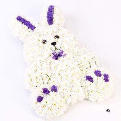This sweet rabbit tribute is created using a mass of white double spray chrysanthemums - rich blue statice and Stems of steel grass. It is trimmed with a coordinating ribbon.