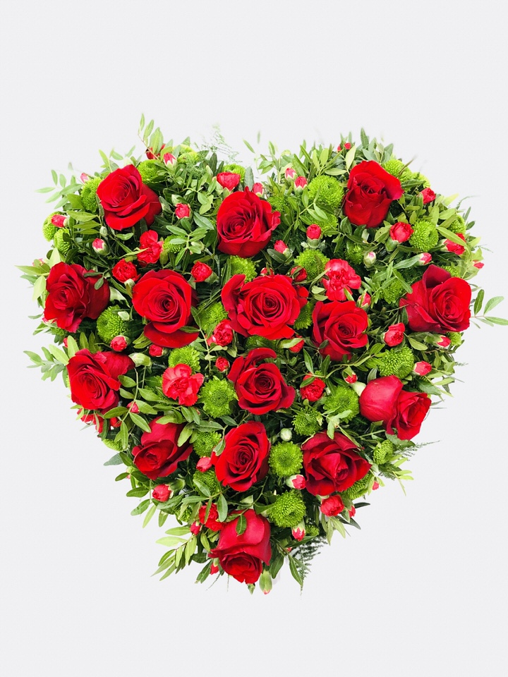 A traditional large heart-shaped design including roses and spray carnations in rich red complemented by choice foliage.