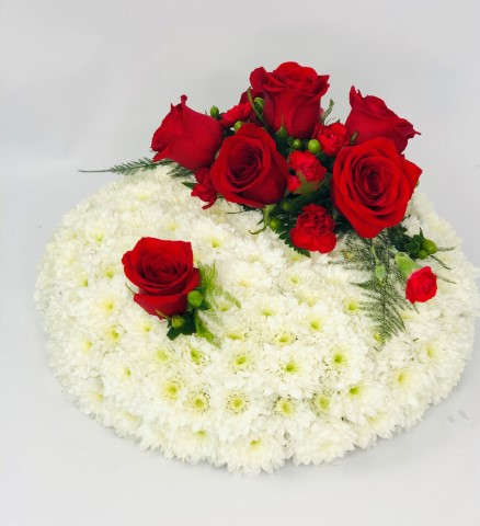A classic posy design created using a mass of white double spray chrysanthemums and completed with a spray of red roses - French ruscus and hypericum berries.