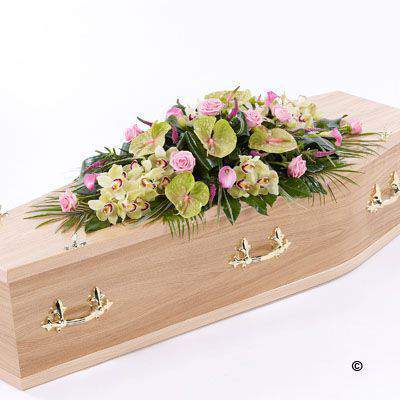 This distinctive casket spray brings together the soft green shades of cymbidium orchids and green anthurium - with delicate pink calla Lily - veronica and large-headed Rose. The spray is finished with aspidistra - aralia leaves - palm leaves and China grass.