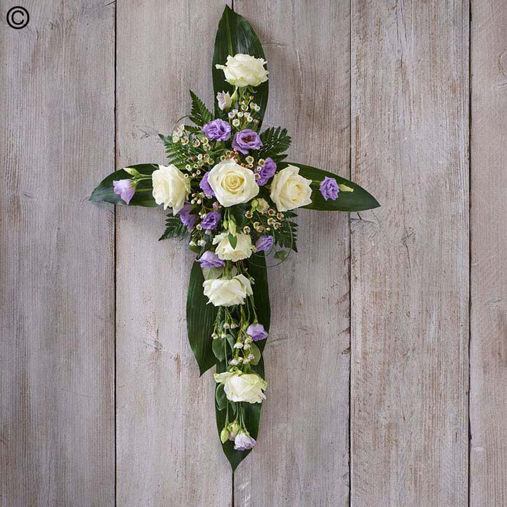 Roses and Dendrobium orchids are arranged on a cross of aspidistra leaves to create this unusual design in cerise, white and green.