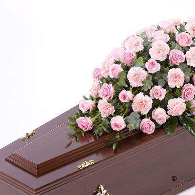 Large-headed pink Rose combine with pink carnations and luxurious foliages to create this traditional large casket spray.