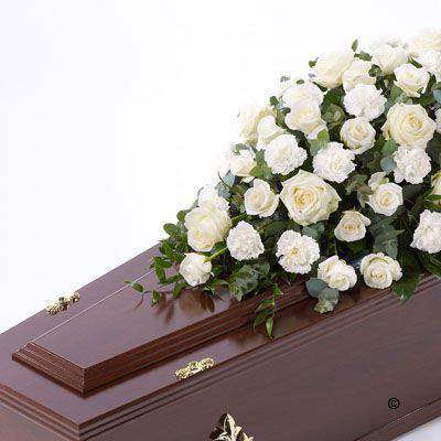 Large-headed white Rose combine with white carnations and luxurious foliages to create this traditional casket spray.