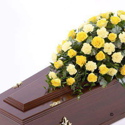 Large-headed yellow Rose combine with yellow carnations and luxurious foliages to create this traditional large casket spray.