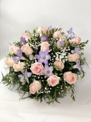 Roses and scented freesia in soft pink and lilac are nestled amongst choice foliage in this classic posy design.