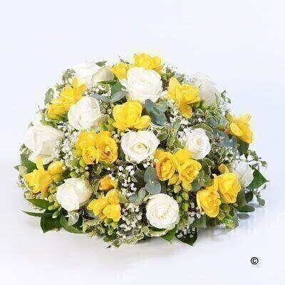 Roses and scented freesia in yellow and white are nestled amongst choice foliage in this classic large posy design.