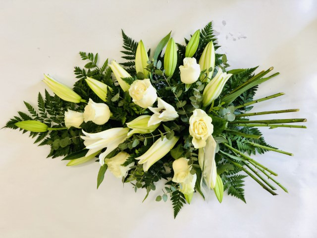 Aralia leaves and French ruscus are nestled amongst classic white Oriental Lily and white large-headed roses in this classic large teardrop spray.