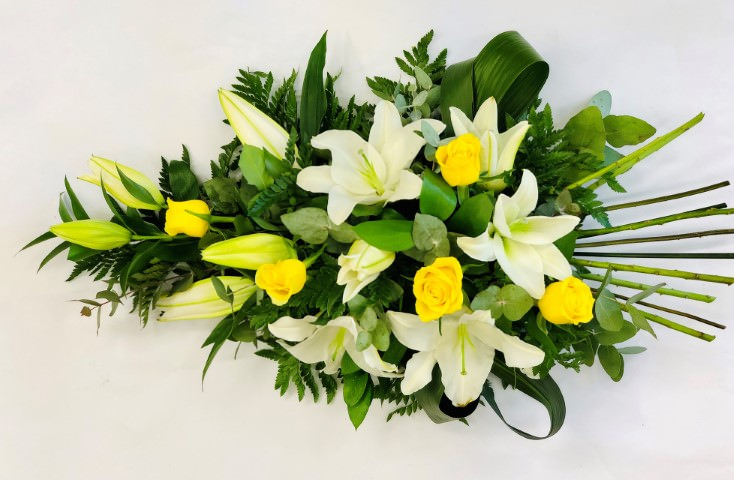 Aralia leaves and French ruscus are nestled amongst classic white Oriental Lily and yellow large-headed roses in this classic teardrop spray.
