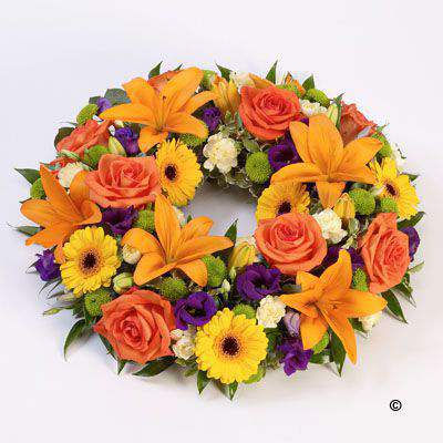 Lily and large-headed roses in orange are nestled amongst yellow germini - green spray chrysanthemums and purple lisianthus in this vibrant circular wreath.