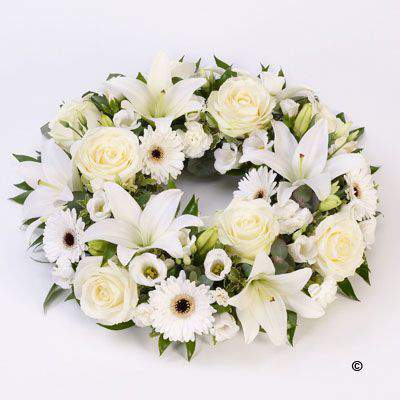 Fresh white Lily and large-headed roses are nestled amongst germini - lisianthus and spray carnations along with contrasting green foliage in this circular wreath.