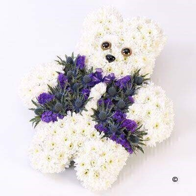 Double spray chrysanthemums - spray carnations - eryngium and statice are used to create this blue and white design shaped like a teddy bear.